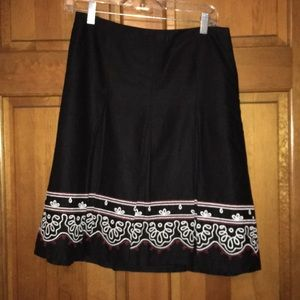 Black skirt with red and white embroidery.
